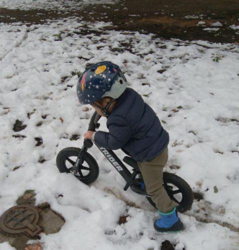 雪の中ストライダーに乗る2歳児